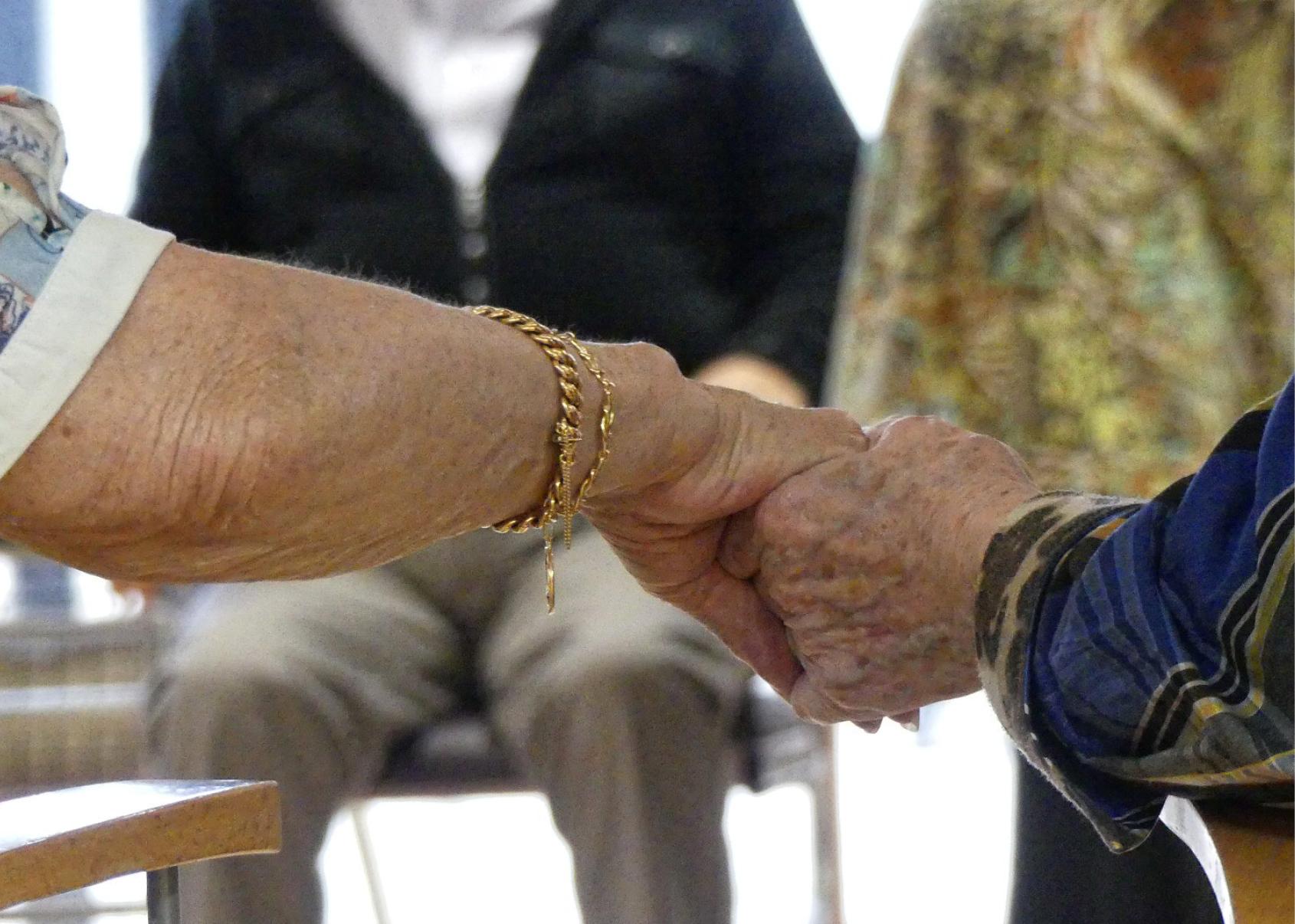 Deux personnes âgées se tenant la main. Photo prise lors d'un projet en lien avec des structures médico-sociales proposées par le Moulin du Roc, Scène nationale à Niort