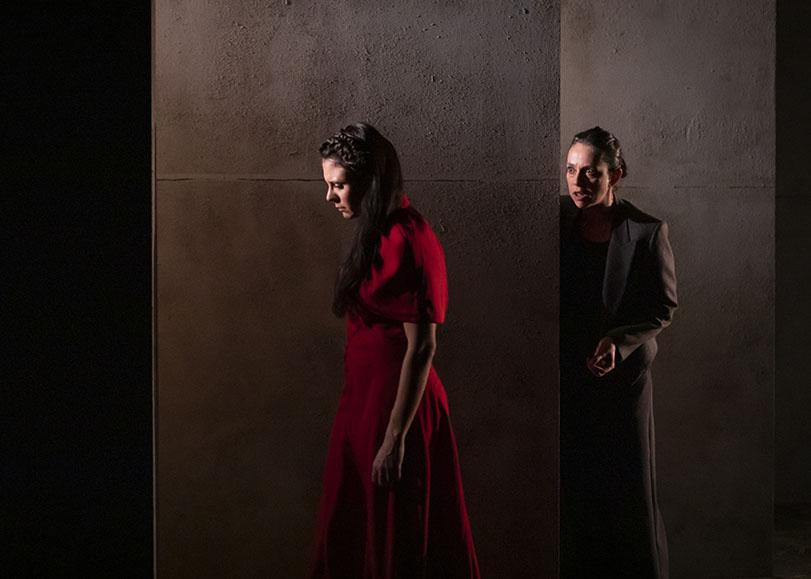 Deux femmes, l'une en robe rouge, l'autre vétue de noir. L'une tourne le dos à l'autre et regardant par terre.