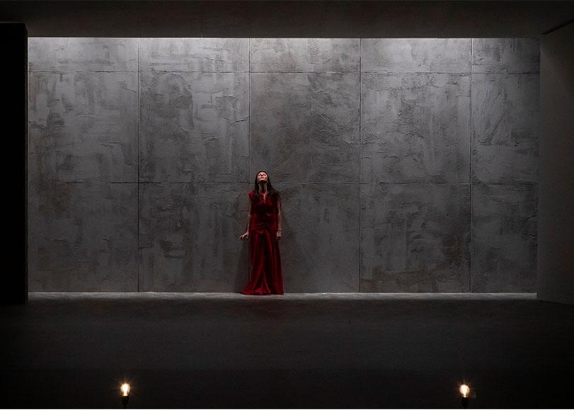 Une femme avec une robe rouge au centre d'un mur sombre. Celle-ci regardant en l'air.