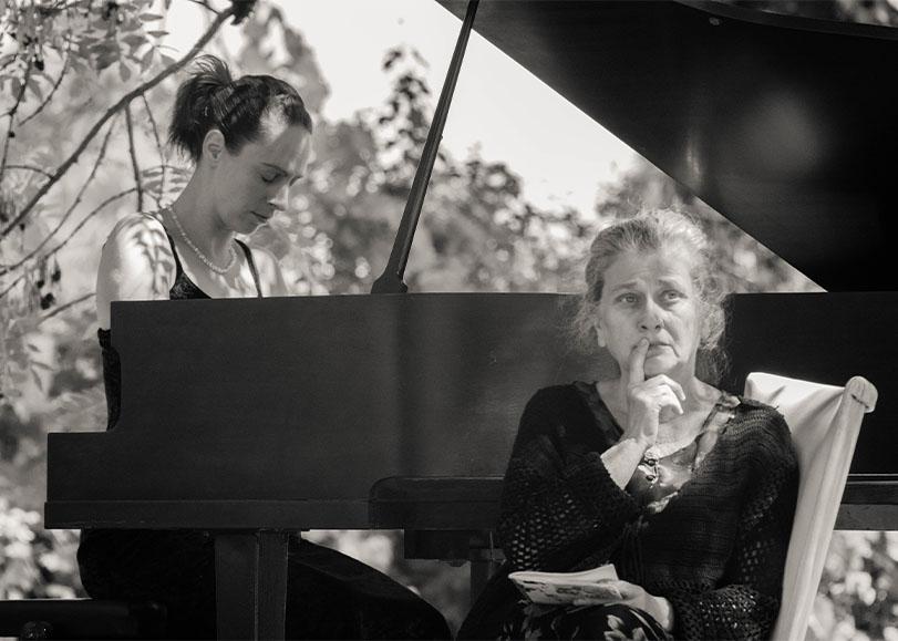 Deux femmes, l'une au piano et l'autre assise regardant au loin.