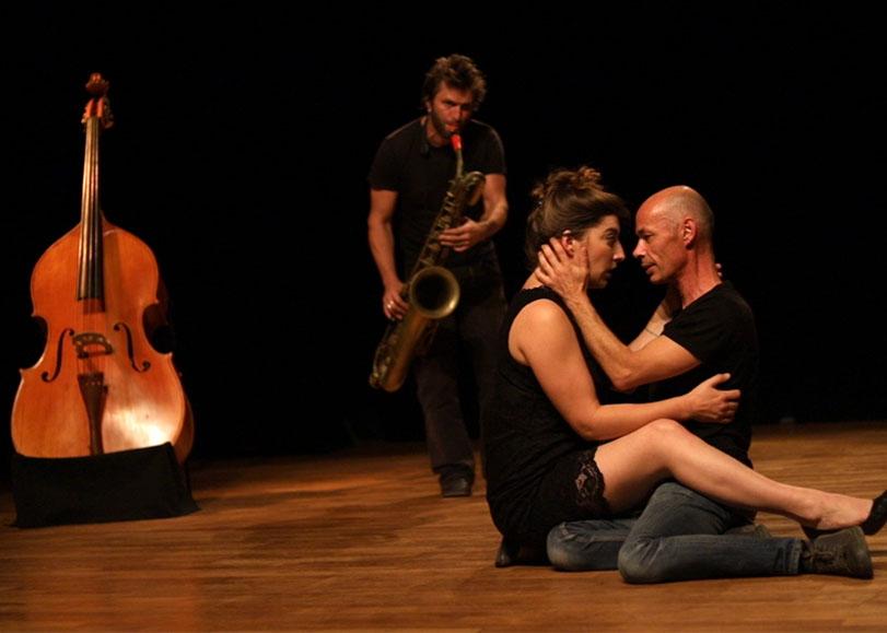 Les deux acteurs du spectacle Des oiseaux dans la glu, assis par terre l'un sur l'autre et face à face, se regardant. Accompagnés derrière eux, d'un musicien jouant du saxophone.