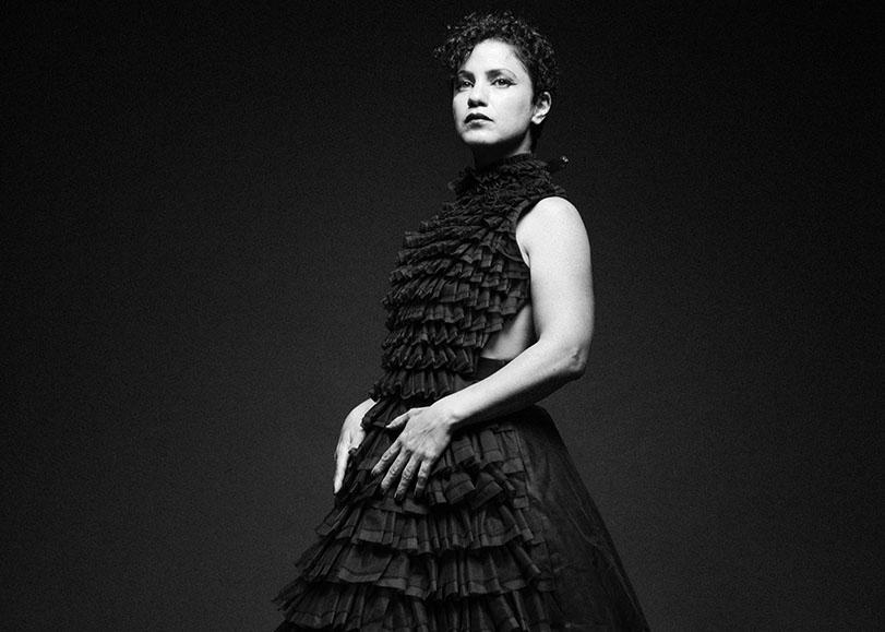 La chanteuse se tient de trois quarts, le regard franc au loin. Vétue d'une robe noir, la chanteuse tient ses main à la taille.