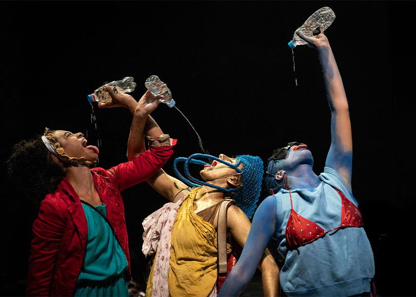 Trois danseurs de Furia, debout, vêtues de couleurs bleue, jaunes et rouge. Ces trois personnages le bras en l'air avec à leurs mains, une bouteille d'eau, où ils boivent la bouche grande ouverte et la langue sortie.