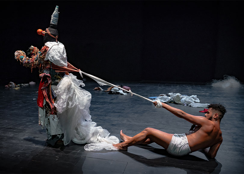Deux danseurs de Furia, l'un vêtu d'un costume tirant un autre qui est à terre, à l'aide d'un corde.