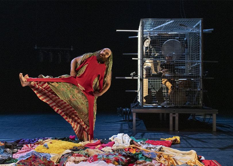 Un homme vétu de robes et costumes, derrière lui un homme dans une cage faisant de la musique.