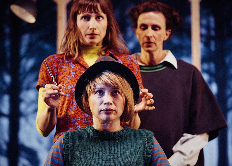 Trois comédiennes du spectacle Jimmy et ses soeurs, l'une d'entre elles est assise les cheveux courts avec un chapeau sur la tête. La comédienne derrière elle, tenant des ciseaux dans les mains et nous regarde.