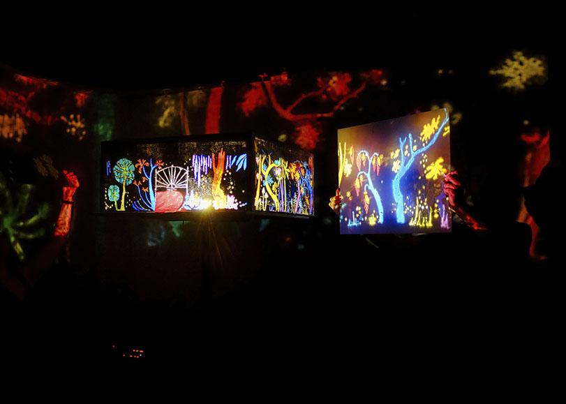 Boite à images dans le noir, projections de dessins aux couleurs rouges, bleus, vertes, jaunes...