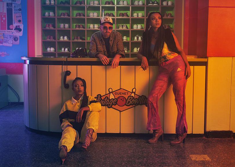 Deux femmes aux cotés d'un hommes. Deux d'entre eux sont accoudés à un comptoir de bowling. Tous vétues de vêtements vintages, styles années 2000.