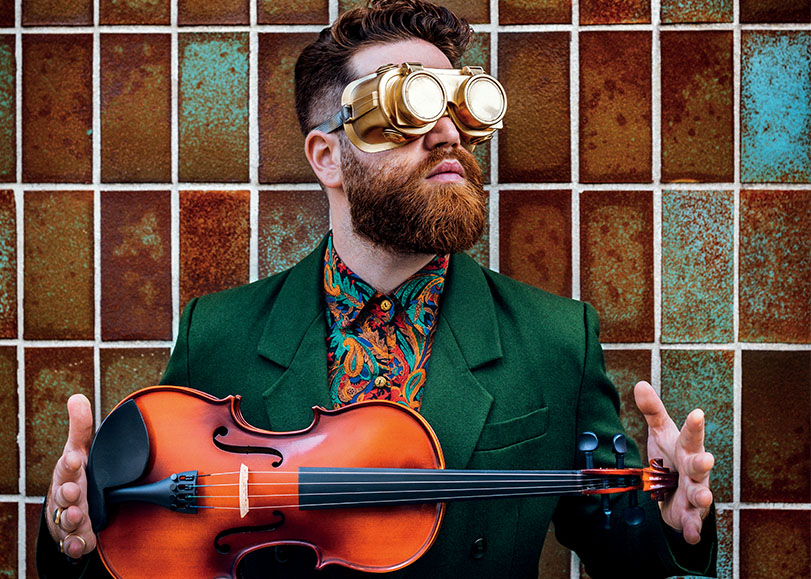 Théo Ceccaldi avec son violon dans les mains. Vétu d'un costume vert et de lunettes atypique