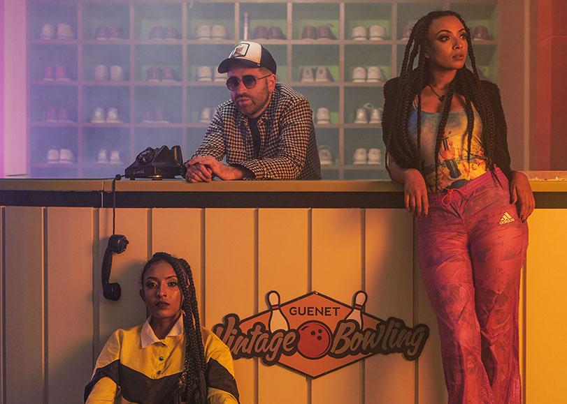 Théo Ceccaldi avec deux femmes, tous accoudés à un comptoir de bowling.