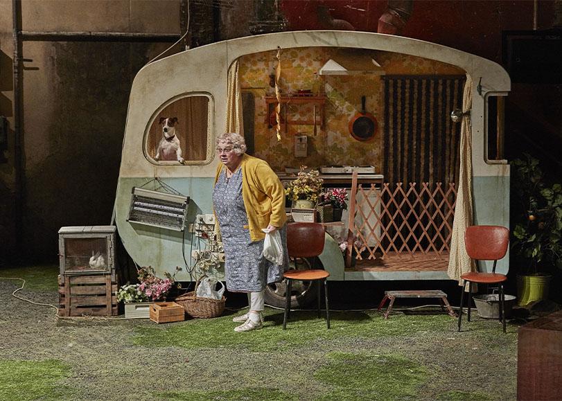 Une comédienne du spectacle La Mouche, devant une caravane avec son chien.