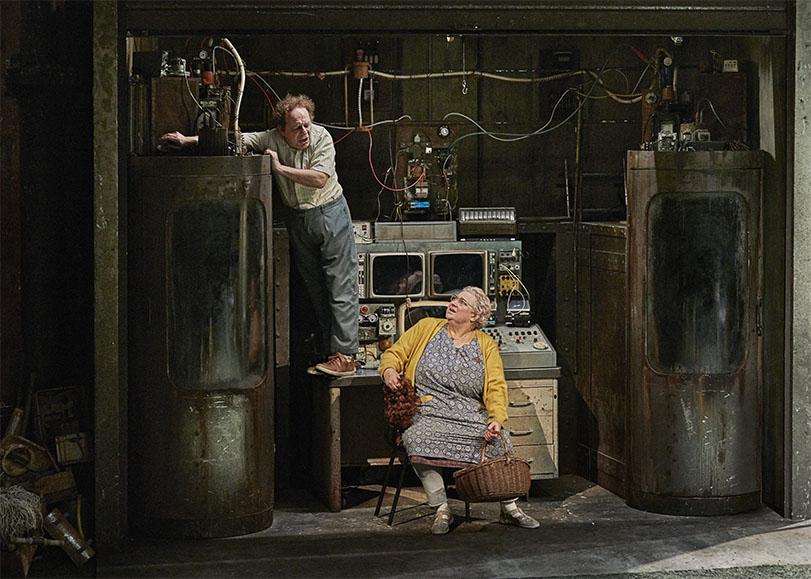 Deux comédiens de la pièce La Mouche, une femme est assise regarde en partenaire de jeu, qui lui est debout sur une table pour trafiquer son invention.