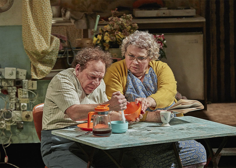 Deux comédiens de la pièce La Mouche, assis à un table prenant le petit déjeuner.