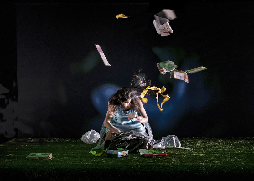 Une femme du spectacle Le joueur de flûte, fouillant dans un sac poubelle et jetant des ordures en l'air.