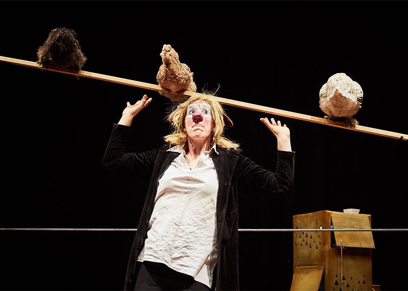 La circassienne Johanna Gallard en habit et maquillage de clown, tenant en équilibre sur sa tête une planche avec ses poules.