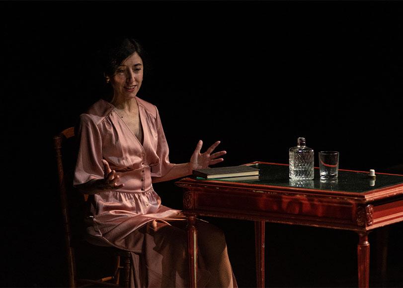 Une femme assise à côté d'un amas de verres à pied. Les tigres sont plus beaux à voir, pièce de théâtre sur l'auteure Jean Rhys programmée auMars-2037, une comédie musicale de Pierre Guillois programmée au Moulin du Roc à Niort