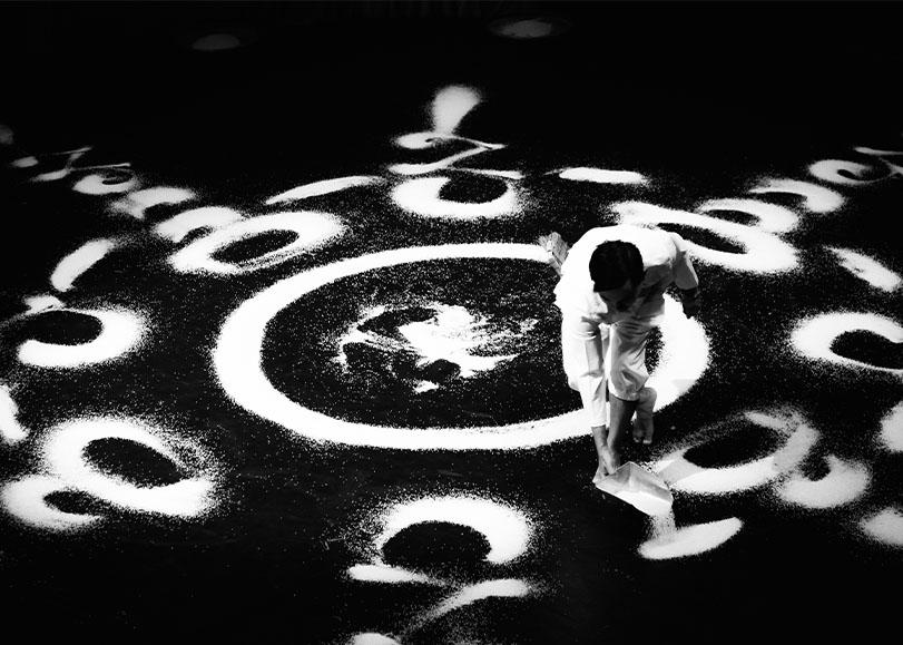 Danseur de L'Or Blanc faisant des formes au sol avec des grains de riz.