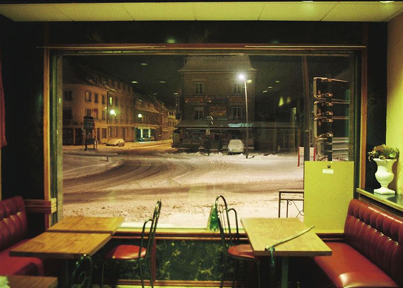 Intérieur d'un café la nuit, avec vu sur la vitrine donnant sur la rue enneigé