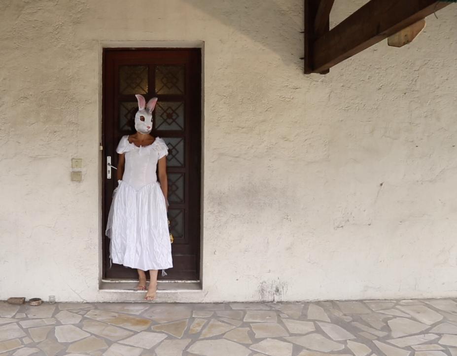Une femme en robe blanche et tête de lapin devant une porte de maison. Projet de danse