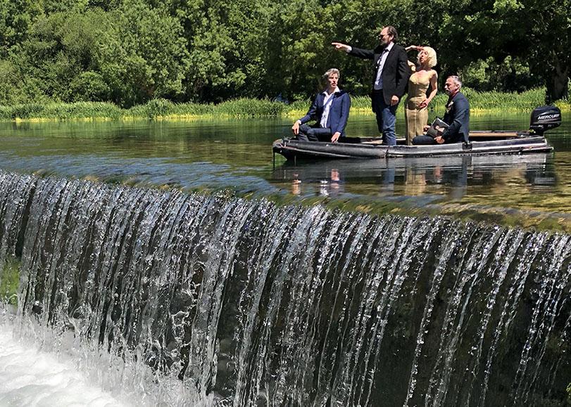 Quatre personnes dans un petit bateau sur un petit barrage de ruisseau.