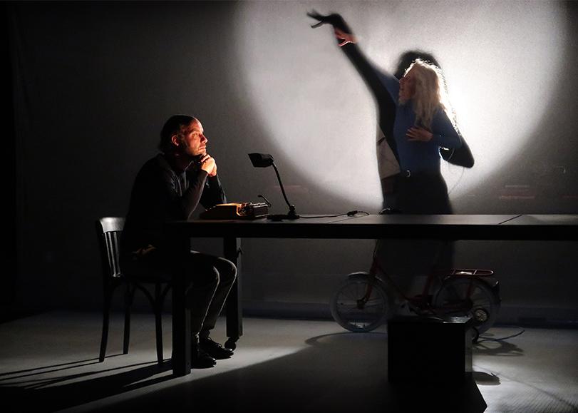 Un homme assis à une table et une femme derrière un rideau transparent. W ou le souvenir d'enfance, une pièce de théâtre à découvrir au Moulin du Roc à Niort