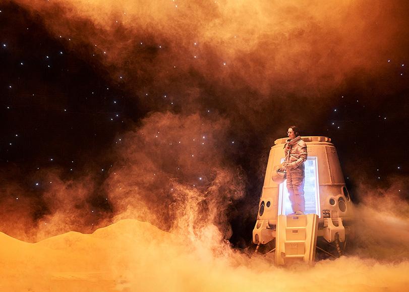 Une femme sortant d'un vaisseau spatial, dans un décor enfumé. Mars-2037, une comédie musicale de Pierre Guillois programmée au Moulin du Roc à Niort