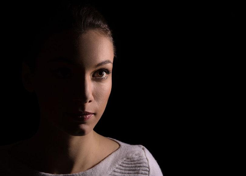La mezzo-soprano Catherine Trottmann sur un fond noir, la moitié du visage dans l'ombre.