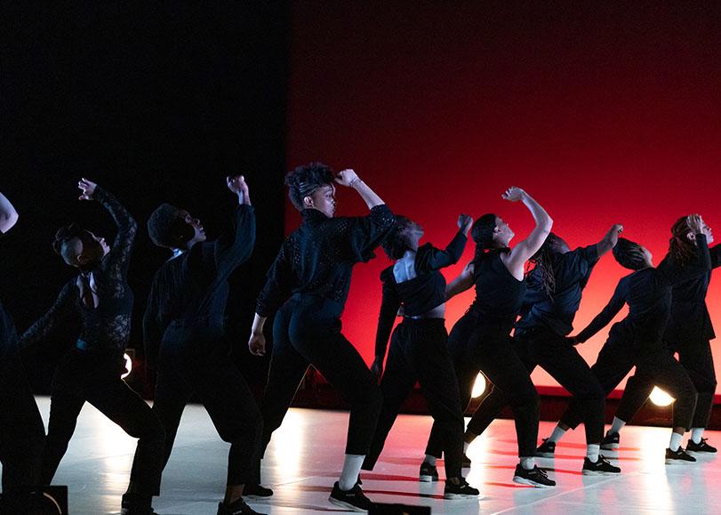Des danseuses disposées en diagoanle, toutes le bras droit levé, le poing fermé. Derrière elles, un fond noir et rouge.