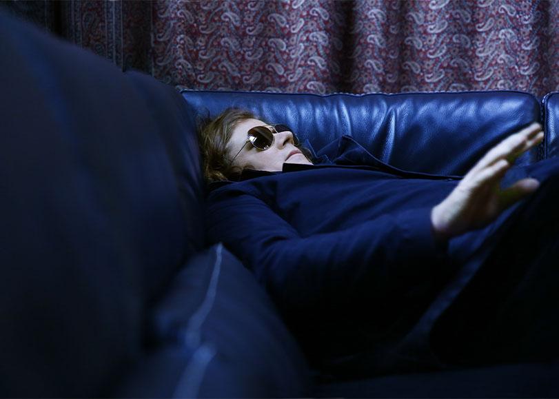 Le chanteur Rover, allongé sur un canapé, vêtu de bleu et de lunettes de soleil.