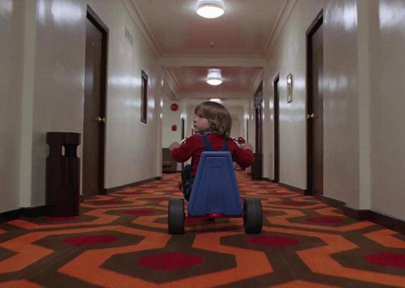 enfant faisant du tricycle dans un couloir shining