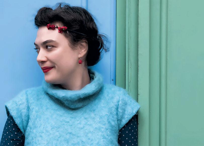La chanteuse Rosemary Standley vétue de bleu etde touche de rouge, adossée à un mur bleu et vert.