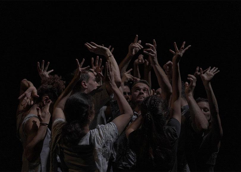 Danseurs de SYMFONIA PIEŚNI ŻAŁOSNYCH qui s'entremêlent les bras en l'air.