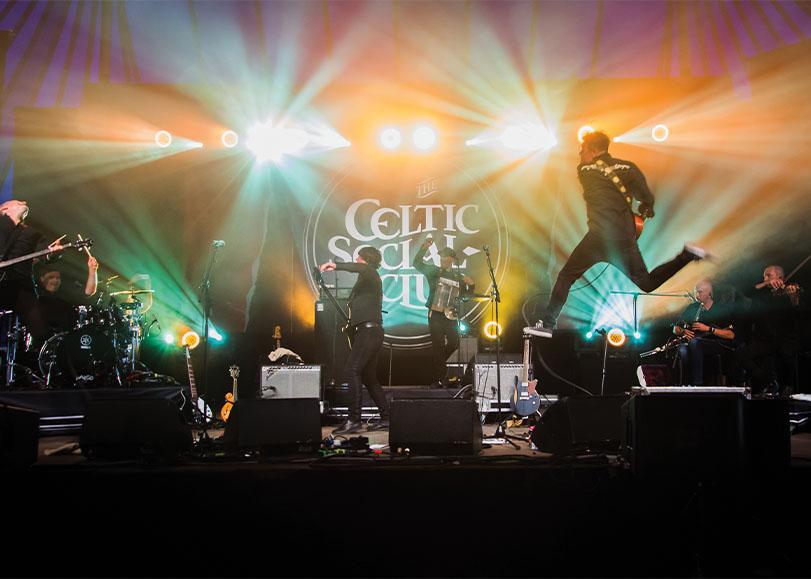 Le groupe de musique Th Celtic Social Club lors d'un concert sur scène.