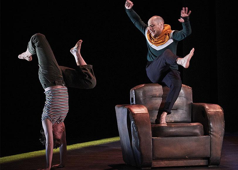 A gauche, une femme debout sur ses mains. A droite, un homme debout sur une jambe sur un fauteuil, les bras en l'air ainsi que son autre jambe.