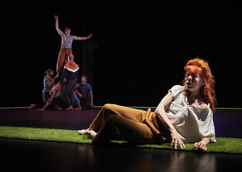 Au premier plan, une femme d'un certain âge allongée au sol. Au second pla, des danseurs faisant des acrobatie type pyramide.
