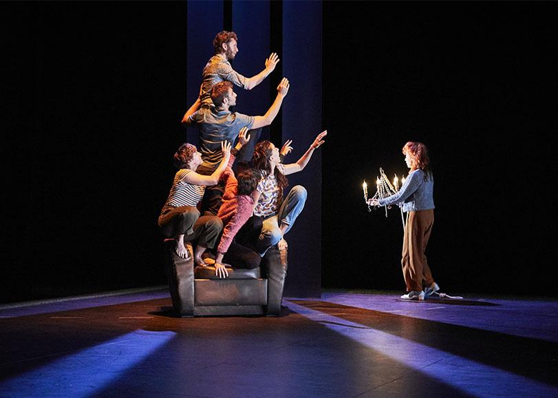 A gauche de la photo, des danseurs accroupies les un sur les autres sur un fauteuil, le bras tendu. A droite, une femme marchant vers aux avec un chandelier à la main.