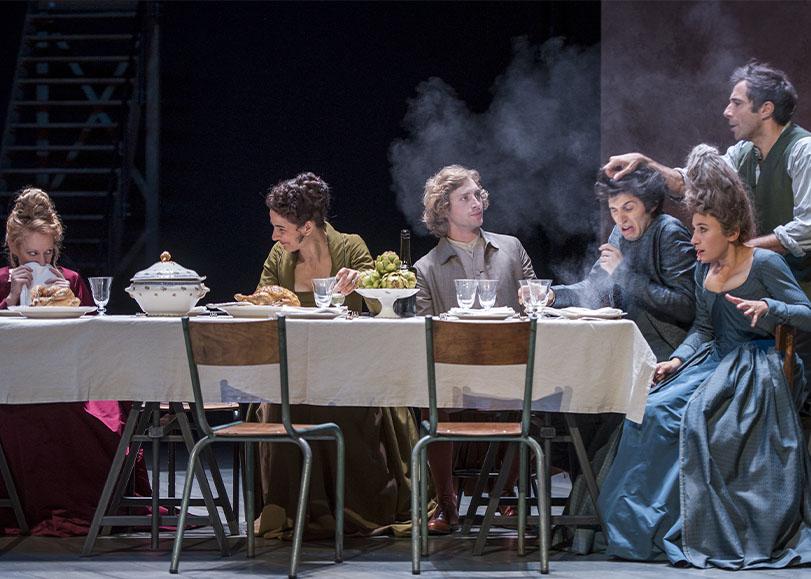 Des hommes et femmes assis autour d'une table discutant et rigolant ensemble. Ces dernirers sont habillés en costumes du XVIII siècle.