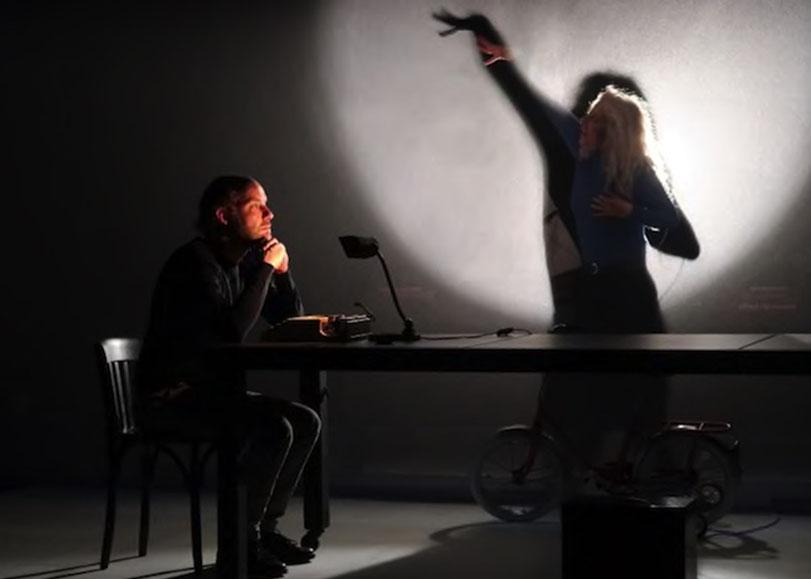 Les deux comédiens du spectacle W. Un homme est assis à une table dans l'ombre et une femme devant lui, debout dans la lumière faisant des gestes avec ses bras.
