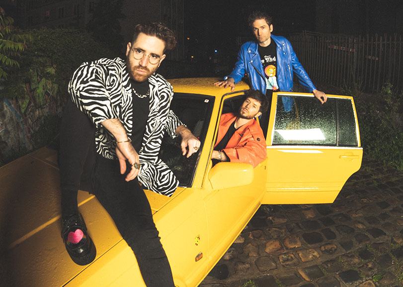 Théo Ceccaldi ainsi que deux autres musiciens du groupe Kimkimkim assis sur une voiture.